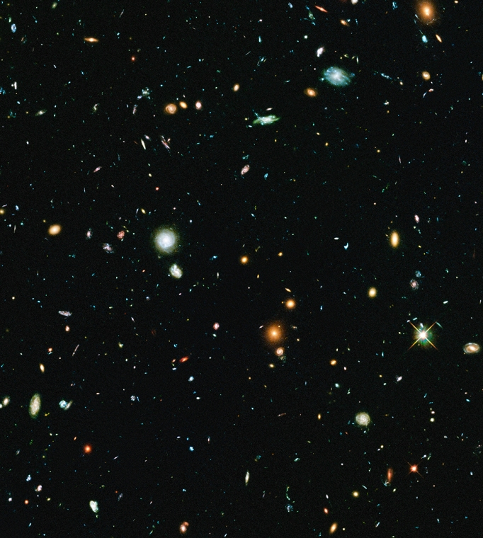 "In this ""parallel field"" to Abell 2744, Hubble resolves roughly 10,000 galaxies seen in visible light, most of which are randomly scattered galaxies. The blue galaxies are distant star-forming galaxies seen from up to 8 billion years ago; the handful of larger, red galaxies are in the outskirts of the Abell 2744 cluster."