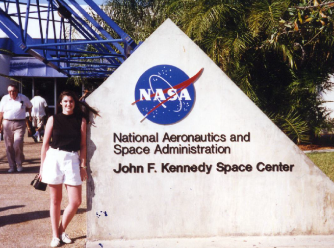 Tricia Royle posing at the sign at the entrance to Kennedy Space Center.