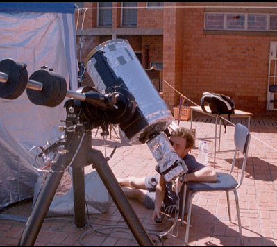 Gabe checks out the telescope for observations of the June 21, 2001, total solar eclipse from Lusaka, Zambia, as part of the Williams College Eclipse Expedition. Credit: J. Pasachoff.
