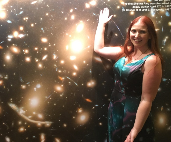 Wearing an astronomically themed dress of her own creation, Rachael poses in front of a large picture of Abell 370.